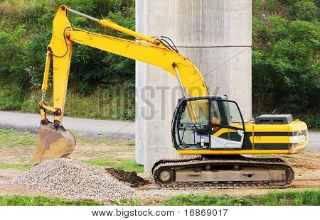 Yellow excavator on a bridge-work