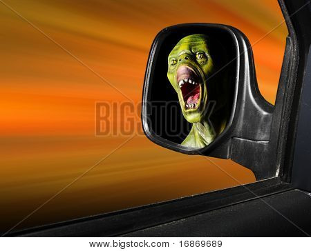 Rear view mirror reflecting fearful monster face - road safety metaphor - green wooden head is unauthorized homemade work.
