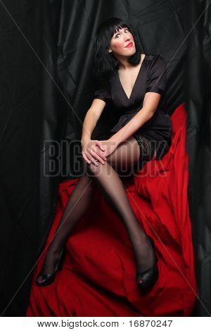 Beautiful brunette woman in black nylons posing on a red  background. Low key studio shot.