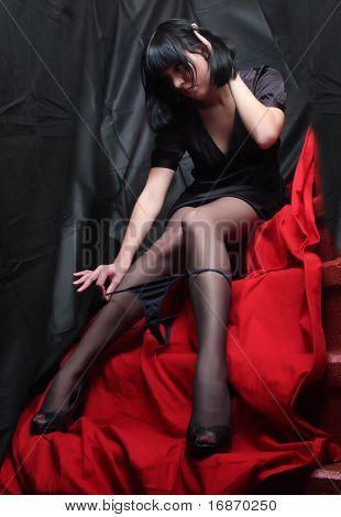 Low key studio shot of slim stripping girl in black nylons on red background