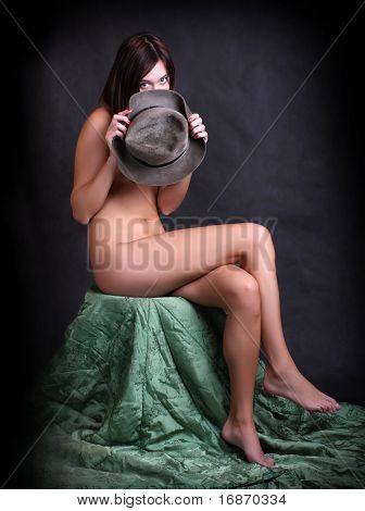 Young naked girl hidden under hat, retro - vintage style studio shot