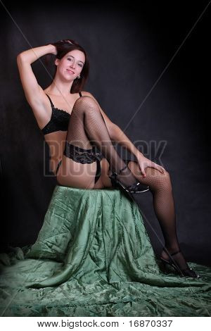 Low key lighting studio shot young attractive women in black sexy lingerie on green brocade background