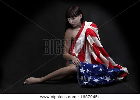Low key studio shot. Young attractive girl dressed in american flag.