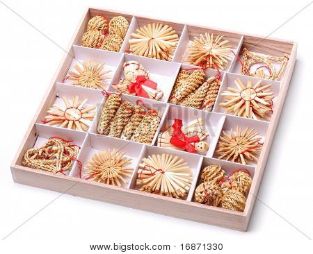 Collection of Handmade christmas decorations from straw, traditional Czech souvenirs in wooden box, isolated on white