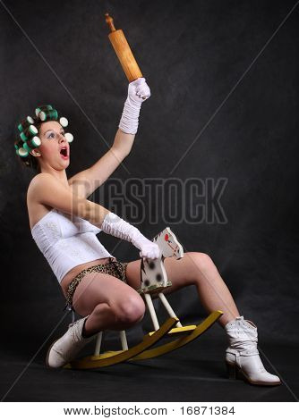 Screaming militant feminist with rolling pin ridden on a wooden hobby horse. Humorous image. Great for calendar.