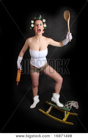 "Screaming militant feminist with ""kitchen weapons"" standing on a wooden hobby horse. Humorous image. Great for calendar."