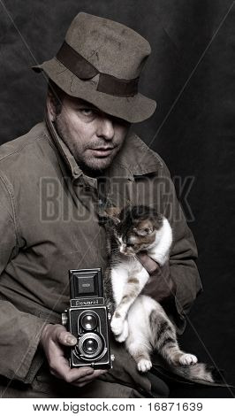 Poor photographer with antique camera (TLR) and spotted cat. Humorous image. Low key studio shot. Great for calendar. Trademark Flexaret is 50 years old - today don't exist. Czech made camera.