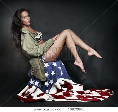 Young attractive girl dressed in old battle coat sitting on american flag. Vintage style studio shot. Great for Independent day advertisign.