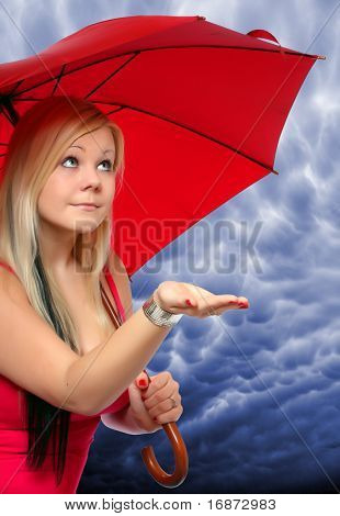 A pretty young girl holding an umbrella checks to see if it is raining, against stormy sky.