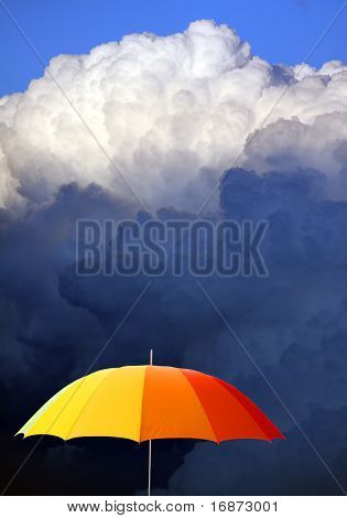 Colored umbrella against stormy sky - conceptual image.