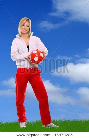 Sporty girl playing soccer against the sky. Great for fitness brochure and advetisements.