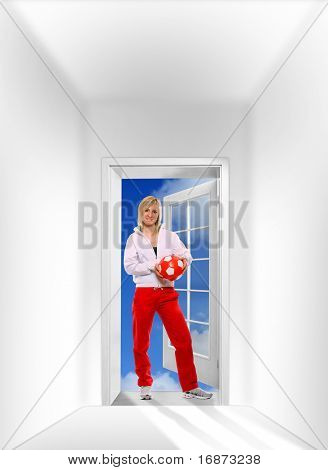 Beautiful sporty girl with soccer ball in opened door against the sky. Great for fitness brochure and advetisements.