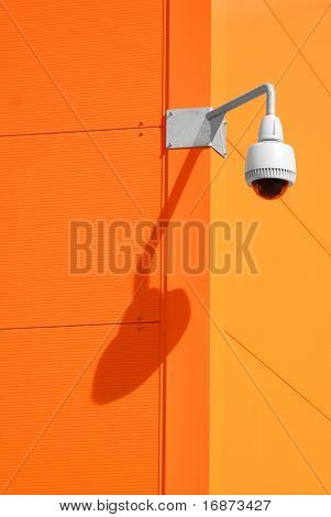 Security camera on orange wall.