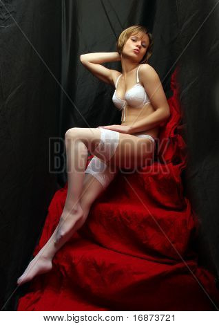 Sitting flirty girl with long slim legs in white nylons. Vintage style low key photography.
