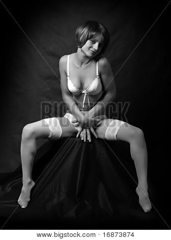 Sitting flirty girl with long slim legs in white nylons. Monochrome low key photography. Great for calendar