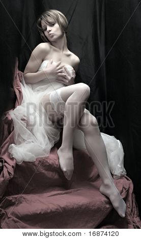 Beautiful slenderness young girl in bridal veil on pink background. Vintage style low key studio shot. Great for calendar.