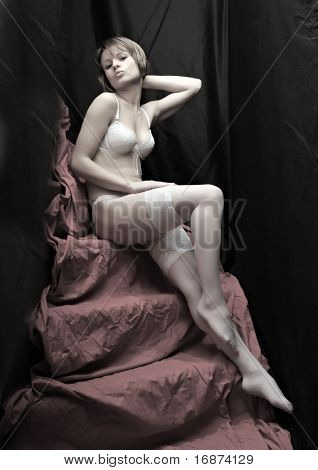 Beautiful slenderness young girl in white nylons on pink background. Vintage style low key studio shot. Great for calendar.