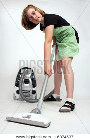 Girl with vacuum cleaner on light grey background - studio shot.