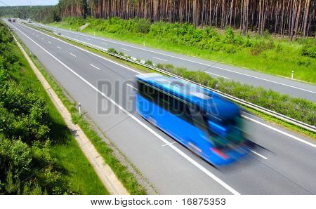 Motion blurred bus on highway. Summer travelling metaphor.