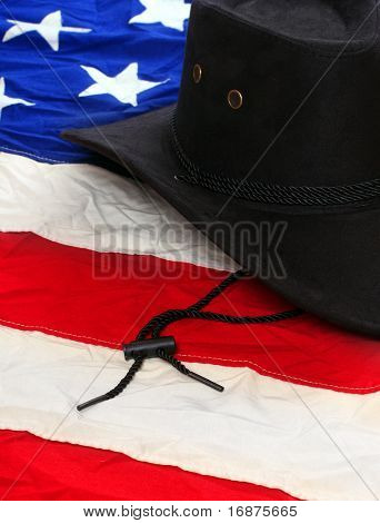Black leather hat on american flag. Traditional hat for all american cowboys. Great image for Independent Day brochures and advertising.
