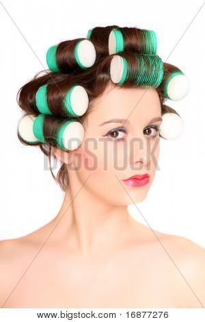 Young beautiful girl is having hair curlers on her head. High key studio portrait.