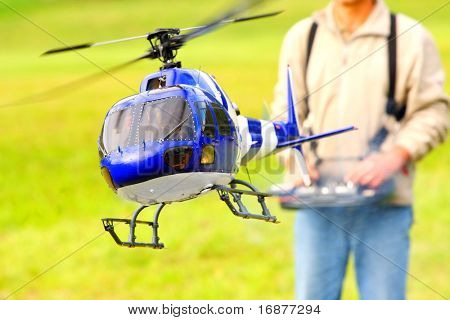 Piloting Radio controlled helicopter (scale-model 1:24 scale) with remote control. Teleobjective shot with shallow DOF.