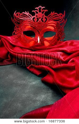 Decorated mask for masquerade on red velvet. Great for halloween brochures and advertisements. Unauthorized homemade paper product.