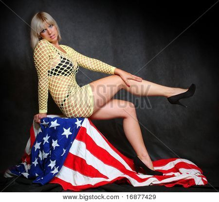 Pretty girl sitting on a american flag. Great for calendar