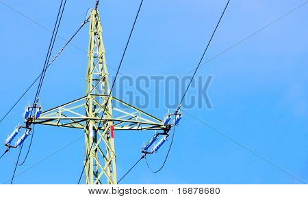 High voltage power tower close up and electrical lines against blue sky.