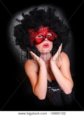 Pretty showgirl with red mask and afro hair-style dancing on the carnival