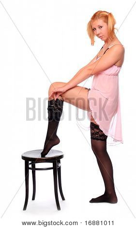Beautiful slenderness young woman in black nylons on a white background.