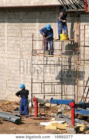 Bricklayers in safety helmets on scaffolding