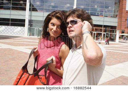 couple at the shopping - woman is waiting on man speaking on the phone