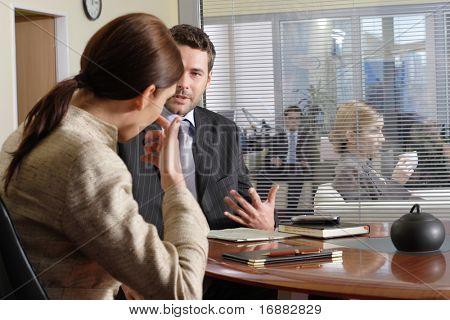Homem de negócios e mulher falando no escritório - outras pessoas no fundo