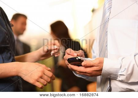 A businessman checks his personal electronic calendar in order to make a new appointment as a co-worker looks on.