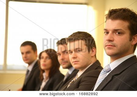 Five business persons in suits sitting at a conference table, taking part in a meeting and/or presentation.