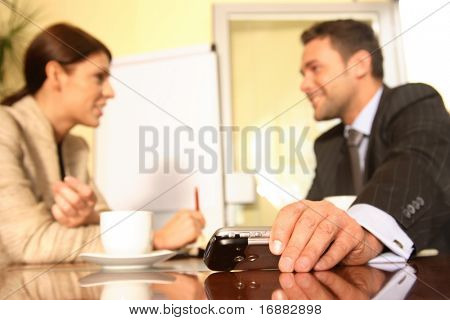 Businessman sitting at a table puts an electronic device aside to concentrate on work being discussed with a female colleague.