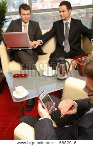 Three young business men siting on leather sofa and working at laptop and palmtop in the office