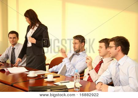 Informal business meeting of five persons - standing woman interview