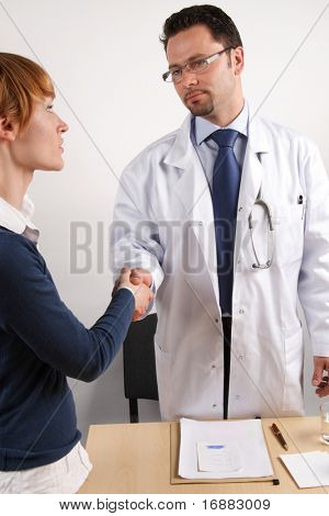 A doctor shakes hands with his patient.