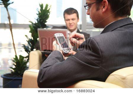 dos hombres de negocios joven emplazamiento en sofá de cuero y trabajando en el ordenador portátil y bolsillo en la oficina