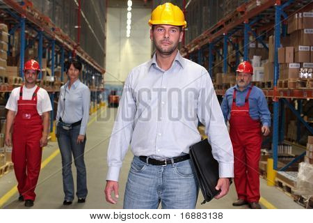 boss with briefcase at the front of team of workforce in warehouse -3 workers in background