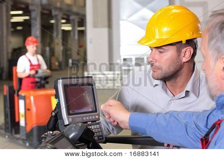 male inspector looking at screen with operator in warehouse