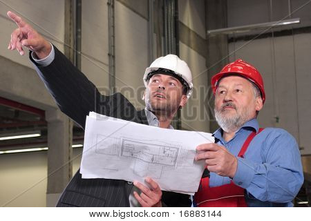businessmen and older worker, wearing hardhats looking at a set of blueprints and discussing a construction project.
