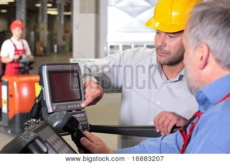 two workers with control panel in factory, third one on forklift in background