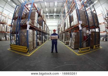 worker in blue uniform with box in the warehouse