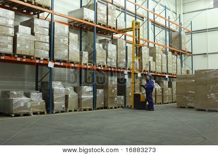 worker in blue uniform counting stocks in warehouse