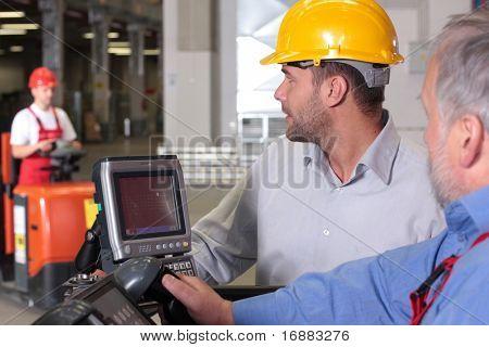 supervisor talking to forklift operator in warehouse
