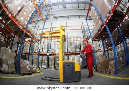 worker in red uniform at work in warehouse in fish-eye lens
