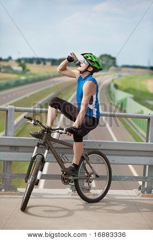 Mountainbiker trinken isotonisches Getränk und Rest über Autobahn